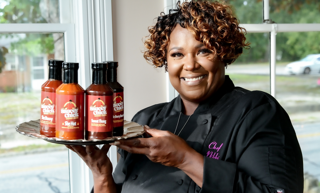 Chef Nikki holding Saucey Chick sauces in bottles on a silver platter