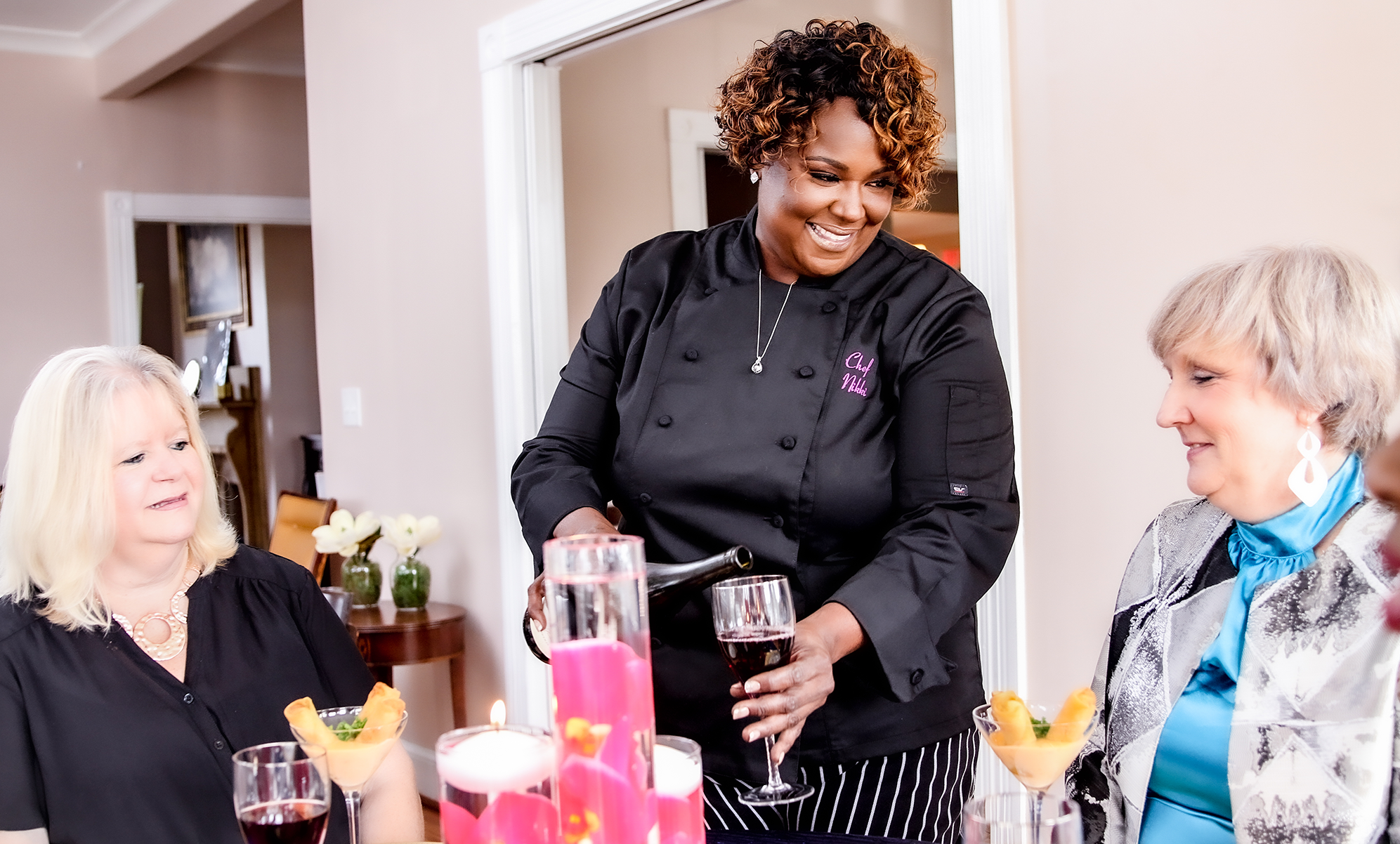 Chef Nikki pouring wine with two white female diners