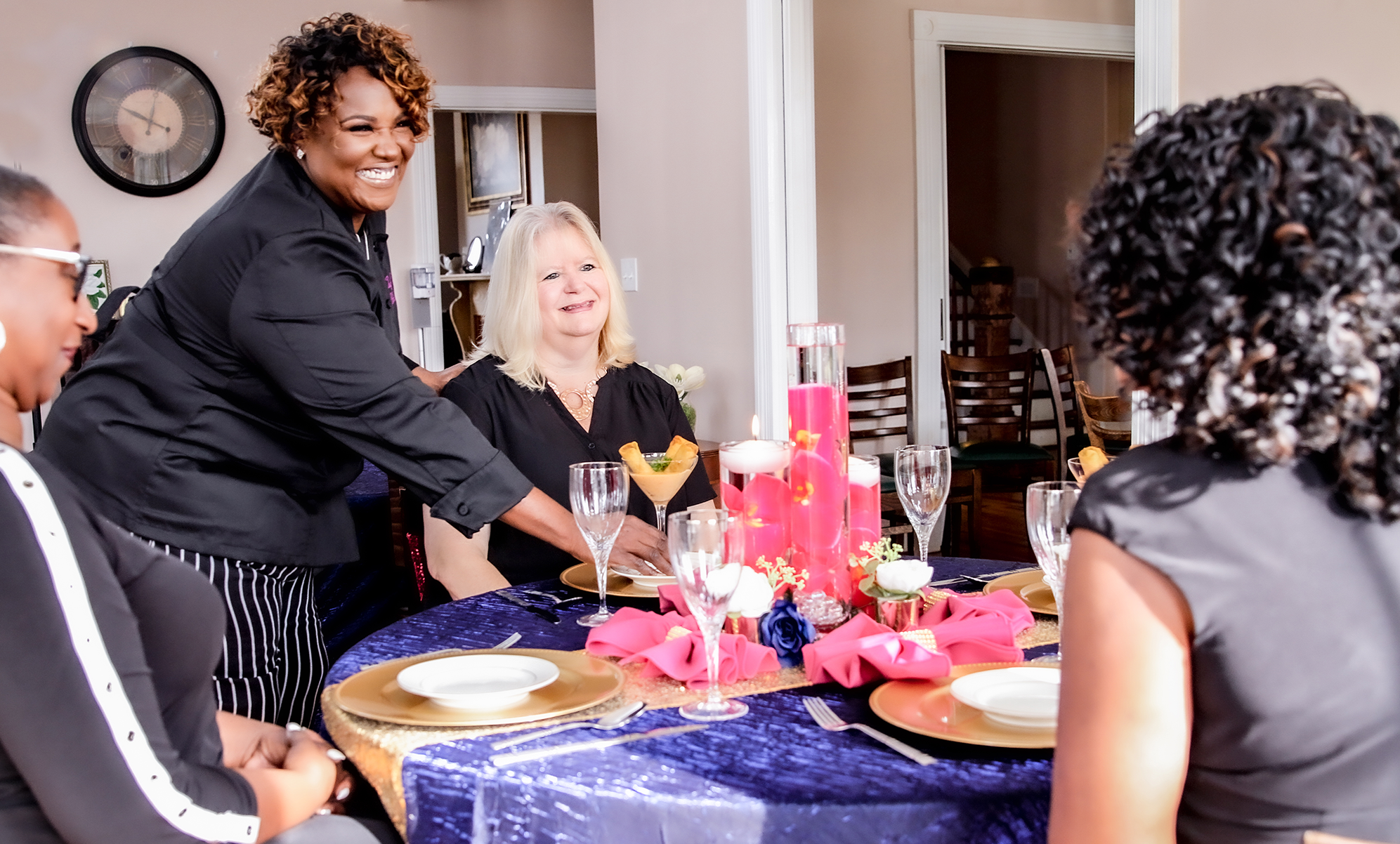 Chef Nikki smiling while pacing food on a plate at a table with a mixed race group of women smiling and patiently waiting