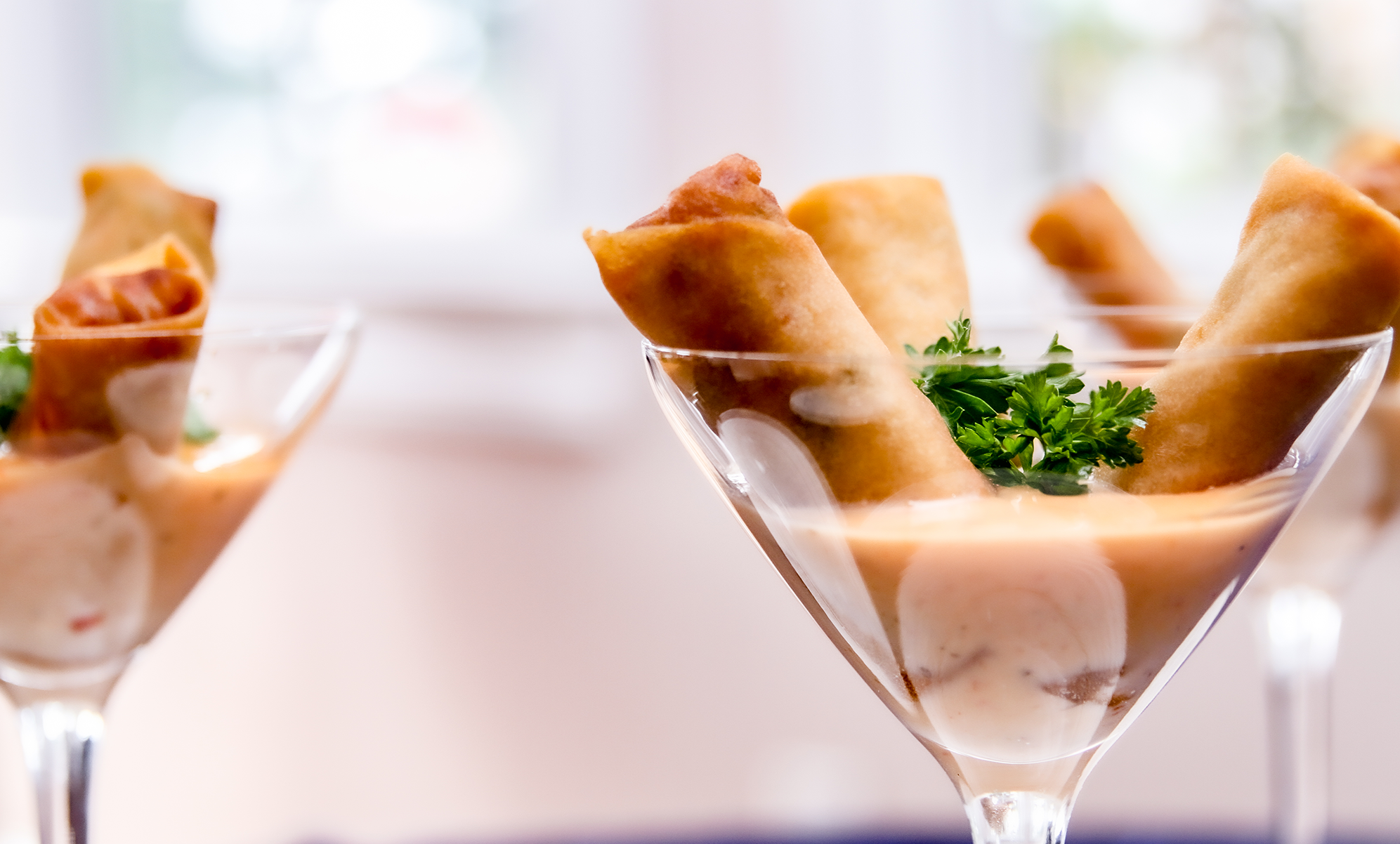 spring rolls in sauce inside a martini glass