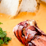 lobster tail in a bowl of soup with parsley for garnish and bread