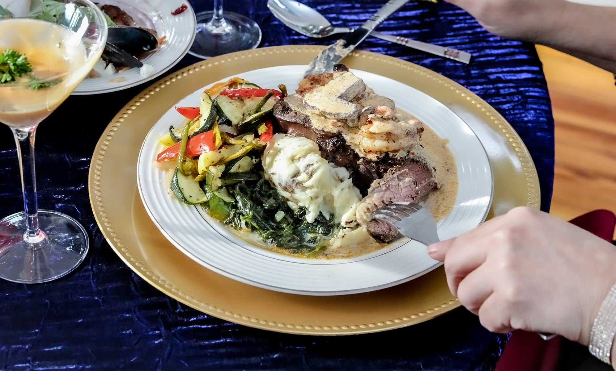white hands using a fork to pick up steak on a plate of food