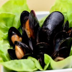 White bowl on a gold plate with half opened mussels