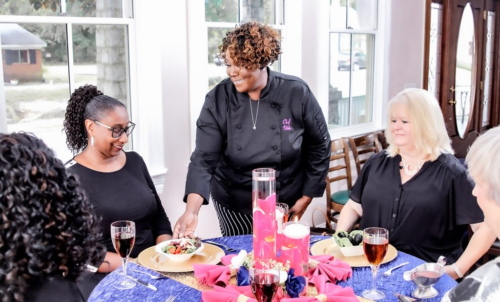Chef Nikki with mixed race clients at a dinner setting