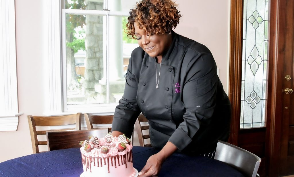 Chef Nikki setting a cake on the table