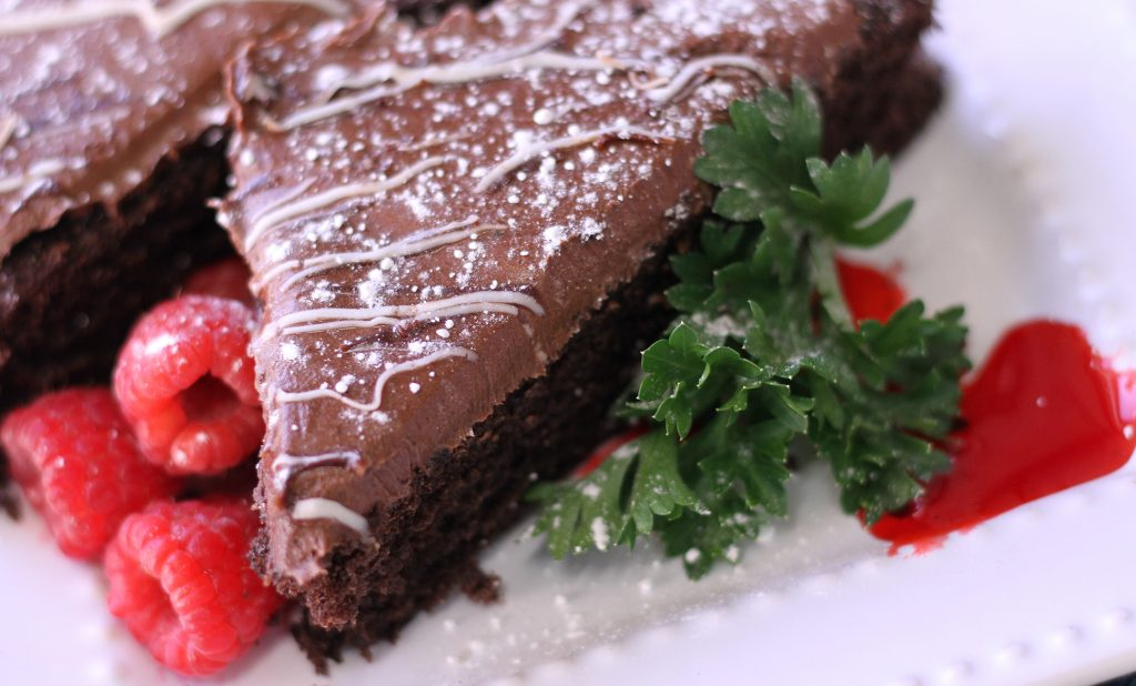 close up of chocolate cake on a plate with powdered sugar and raspberries