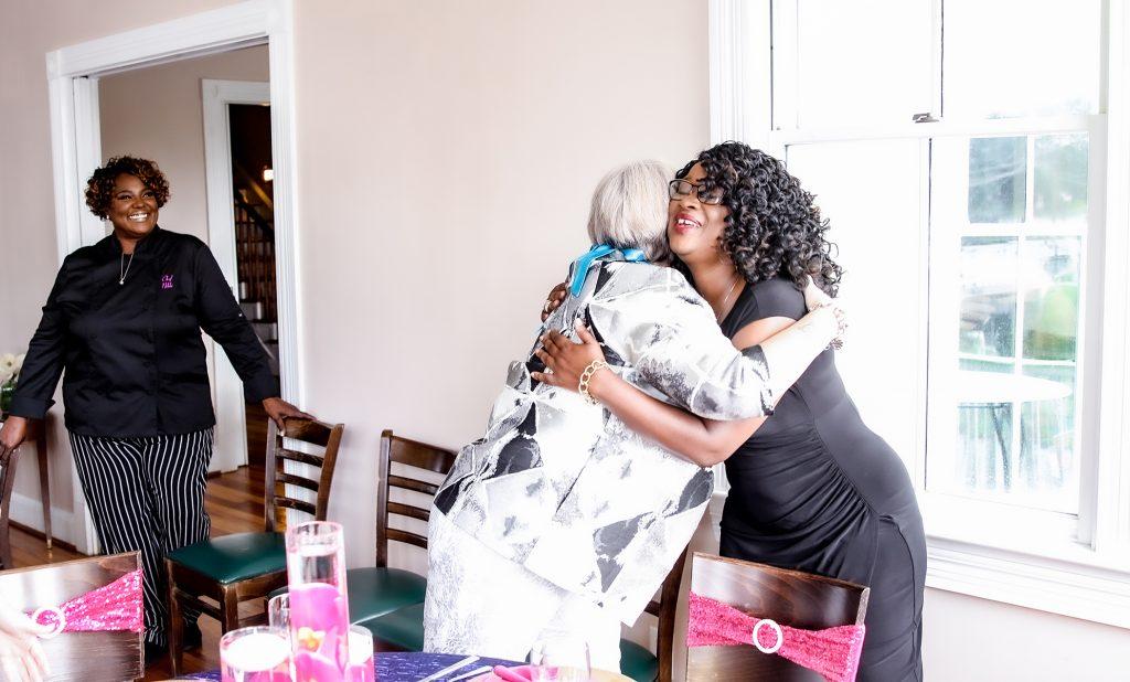 Chef Nikki smiling while viewing hugging women after enjoying her food