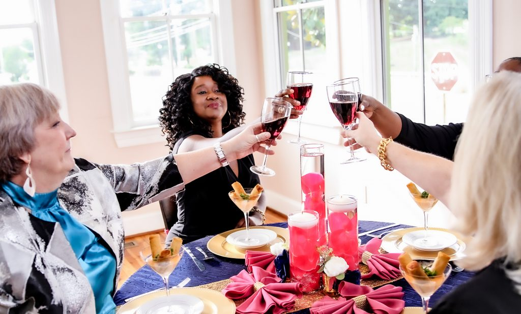 mixed race group of women sharing wine with glasses raised for a toast