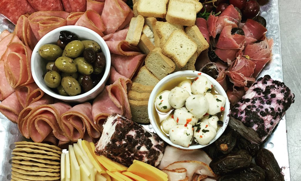 cold cuts. crackers, and olives on a platter