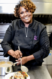 Chef Nikki pouring sauce on a plate of food